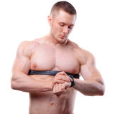 Shirtless athlete man looking at heart rate watch. Royalty Free Stock Photography