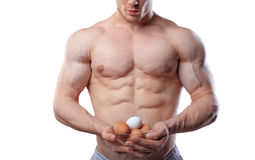 Shirtless athlete man showing cup with eggs at isolated white background Royalty Free Stock Image