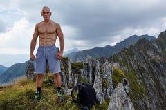 Shirtless athletic man on mountain top Stock Photos