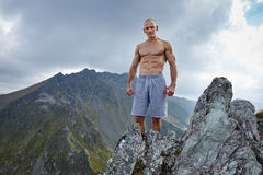 Shirtless athletic man on mountain top Royalty Free Stock Photos