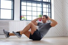 Middle age man doing stomach workouts. Shirtless athletic middle age man doing stomach workouts on a floor Stock Photos