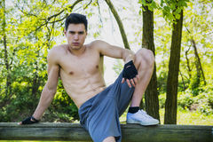 Shirtless athletic young man resting in city park Royalty Free Stock Images