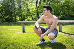 Shirtless athletic young man resting in city park Stock Photography