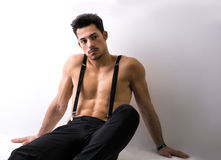 Shirtless athletic young man with suspenders sitting on floor Stock Images