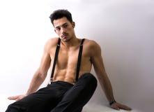 Shirtless atletische jonge mens die met bretels op vloer zitten stock afbeeldingen