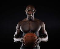 Shirtless basketbalspeler die camera het glimlachen bekijken Stock Foto