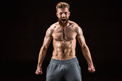 Shirtless bearded bodybuilder posing and yelling isolated on black Royalty Free Stock Photography