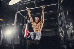 A man doing stomach exercises on a horizontal bar. Shirtless bearded man doing stomach exercises on a horizontal bar Royalty Free Stock Photos