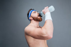Shirtless bearded sportsman drinking water from plastic bottle Stock Photos
