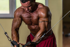 Shirtless body builder doing standing press white cable for chest Royalty Free Stock Photo