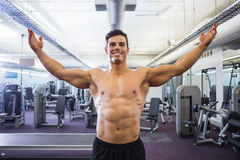 Shirtless bodybuilder with arms raised in gym Royalty Free Stock Image