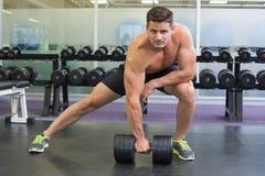 Shirtless bodybuilder die zware zwarte domoor in opheft valt uit Stock Afbeeldingen