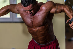 Shirtless bodybuilder doing standing press white cable for chest Stock Image