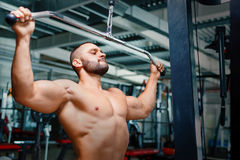 Shirtless bodybuilder exercising. Young athlete man on arm press machine on a gym background. Muscle building concept. A perfect muscular young man with a six Royalty Free Stock Image