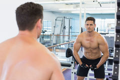 Shirtless bodybuilder flexing in front of the mirror Royalty Free Stock Photo