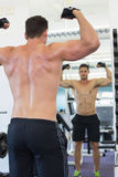Shirtless bodybuilder flexing in front of the mirror Stock Photos