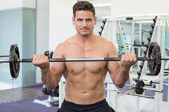 Shirtless bodybuilder lifting heavy barbell weight looking at camera Royalty Free Stock Images