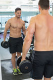 Shirtless bodybuilder lifting heavy black dumbbell looking in mirror Stock Photo