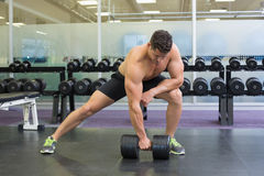 Shirtless bodybuilder lifting heavy black dumbbell in a lunge Royalty Free Stock Photo