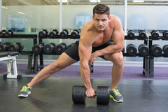 Shirtless bodybuilder lifting heavy black dumbbell in a lunge Stock Images