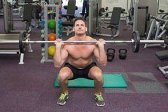 Shirtless bodybuilder lifting up heavy barbell weight Stock Photos