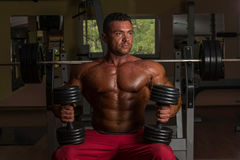 Shirtless bodybuilder posing with dumbbell at the bench Stock Images