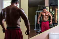Shirtless bodybuilder posing at the mirror Royalty Free Stock Photo