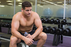 Shirtless bodybuilder sitting on bench with water bottle Royalty Free Stock Images