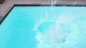 Shirtless boy jumping into swimming pool