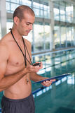 Shirtless coach with stopwatch by pool at leisure center Stock Photos