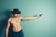 Shirtless cowboy with a gun Stock Photo