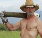 A Shirtless Cowboy Shoulders a Fence Post Driver Royalty Free Stock Image