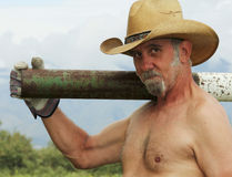 A Shirtless Cowboy Shoulders a Fence Post Driver Stock Photo