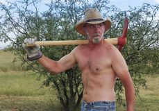 A Shirtless Cowboy Shoulders a Red Pickax Royalty Free Stock Image
