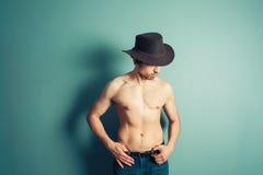 Shirtless cowboy striking a pose by blue wall Royalty Free Stock Photo