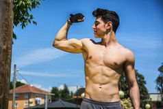 Shirtless fit athletic young man doing bicep pose Royalty Free Stock Images