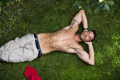 Shirtless fit male model relaxing lying on the grass Royalty Free Stock Image