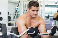 Shirtless focused bodybuilder lifting heavy barbell weight using bench Stock Photography