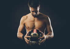 Shirtless football player with helmet. Attractive shirtless football player holding protective helmet and posing Royalty Free Stock Photography