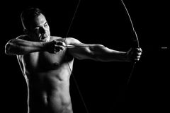 Shirtless guy aiming with a bow and arrow Royalty Free Stock Images
