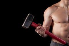 Shirtless guy holding a sledgehammer. Torso of a shirtless guy holding a sledgehammer royalty free stock image