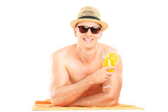 Shirtless guy lying on towel and drinking a cocktail Royalty Free Stock Image