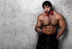 Shirtless guy with perfect body. Bodybuilder. Man with red headset Royalty Free Stock Images