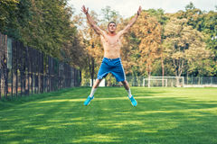 Shirtless handsome man working out in park, cross fit training. Athletic man jumping and doing exercises outdoor