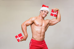 Shirtless macho man in santa hat holding gifts. Portrait of shirtless macho man in santa hat holding gifts over white background Royalty Free Stock Photo
