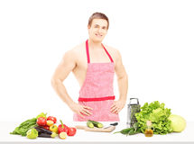 Shirtless male with apron preparing salad Stock Photos