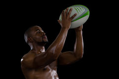 Shirtless male athlete catching rugby ball Stock Images