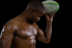 Shirtless male athlete flexing muscles while holding rugby ball Royalty Free Stock Photography