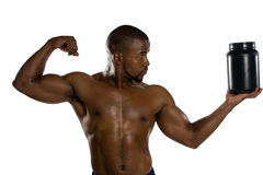 Shirtless male athlete flexing muscles while holding supplement jar. Against white background Royalty Free Stock Photo