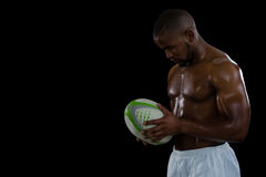 Shirtless male athlete holding rugby ball Stock Image